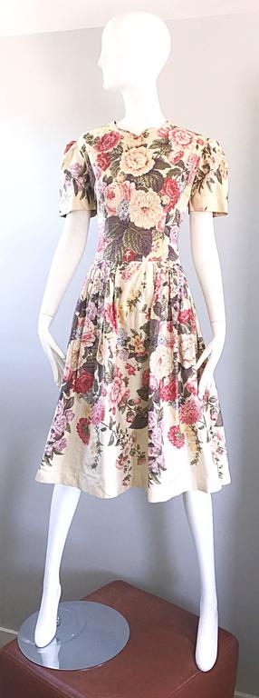 Gorgeous 80s does 50s hand painted demi couture cotton puff sleeve dress! Features handpainted flowers in pink, purple, yellow, green and ivory on an ivory background. Impeccable construction, with so much attention to detail. Most of the