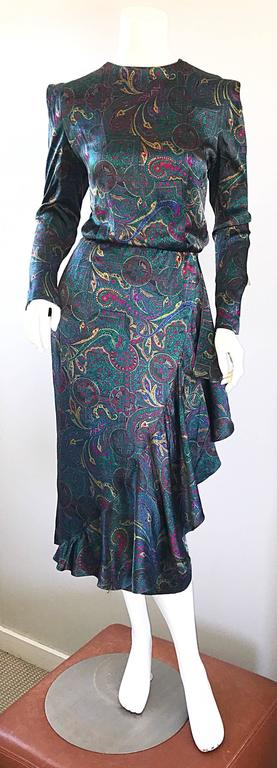 Pretty vintage LOUIS FERAUD emerald jewel tone long sleeve silk dress! Features fantastic paisley prints in emerald green, fuchsia pink, blue, and yellow. Sleek slim bodice with a flamenco style skirt that features an oversided ruffle down the left