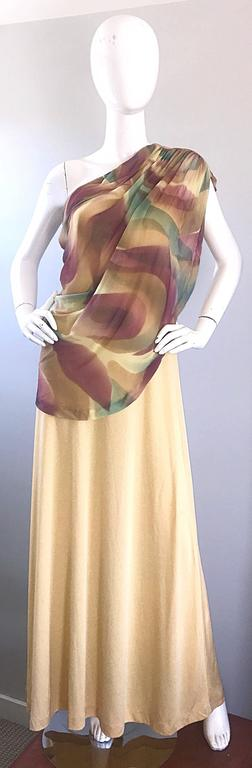 Unbelievable 1970s JOY STEVENS one shoulder Grecian gown! Features a golden jersey body with plenty of stretch. Chiffon overlay features purple, green and gold abstract print. Hidden zipper up the side with hook-and-eye closure. Great with sandals