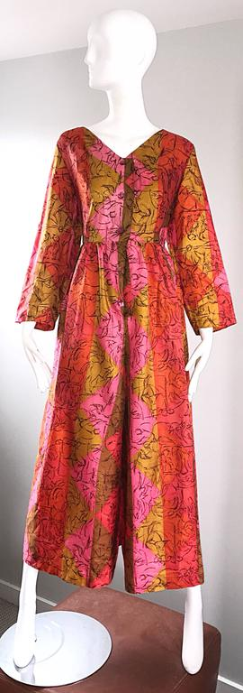 Amazing 1970s wide leg / palazzo cropped culottes jumpsuit! Features vibrant colors of hot pink, orange, and burnt orange throughout. Fabulous scribble print in black. Pink iridescent buttons up the bodice, with a hook-and-eye closure at waist and