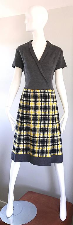 Chic 1960s yellow, grey, black and white plaid wrap style A line dress! Features a fitted charcoal gray bodice, with a wool boucle bell shaped skirt in a tartan plaid. Interior snaps and hook-and-eyes shut at side interior, and at bust. Demi couture