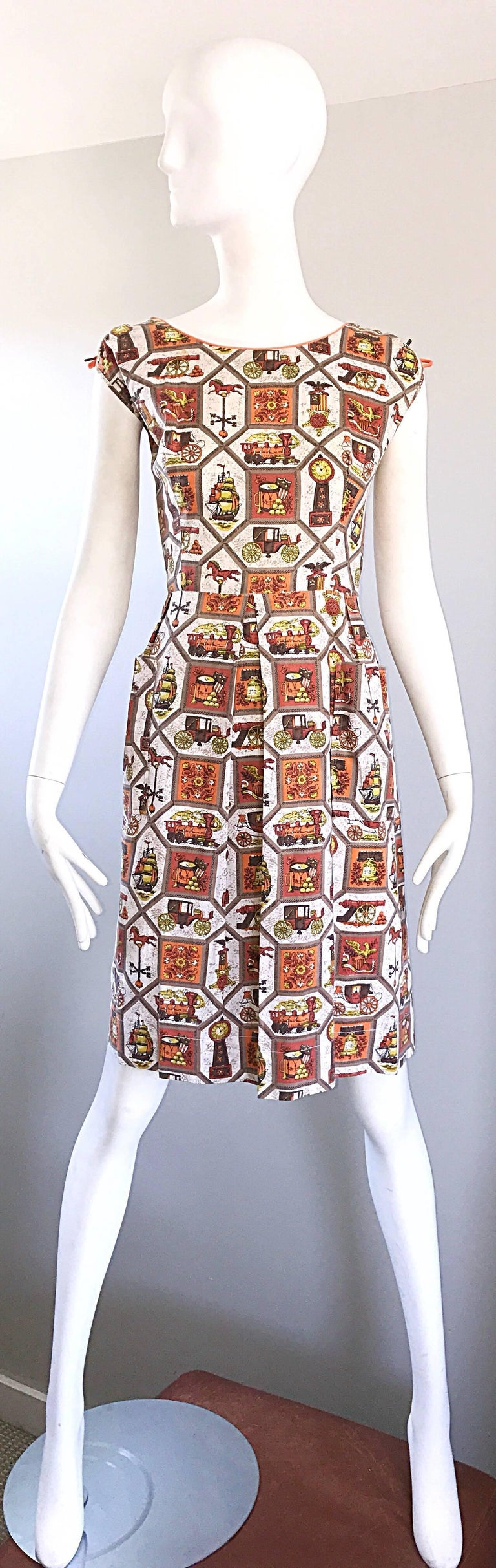 Chic and rare larger plus size 1950s novelty cotton dress! Features whimsical prints of trains, toy horses, drums, clocks, flowers, ships, cannons, crests, etc. Vibrant colors of orange, brown, yellow, gold, brown and burnt orange throughout. Bright