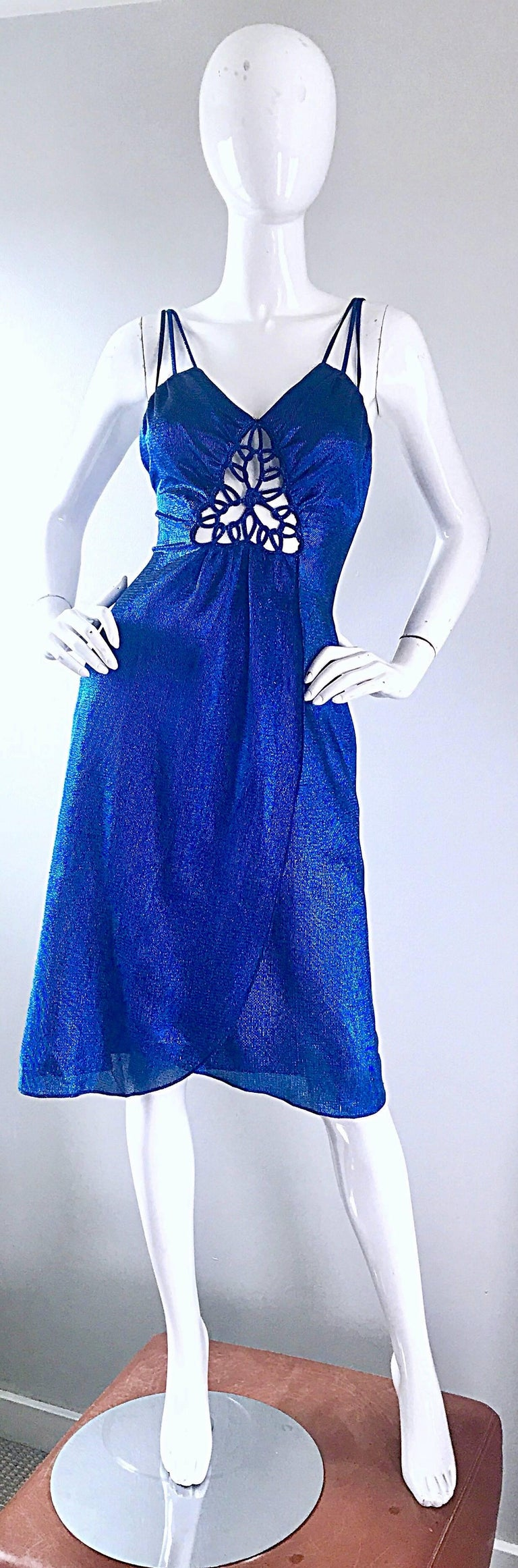 Sexy 1970s SAMIR electric blue metallic slinky cut-out dress! Features an intricately cut-out detail at center bust. Hidden zipper up the back. Three straps at each shoulder. Flattering flirty wrap style skirt, with a fitted bodice. Looks amazing