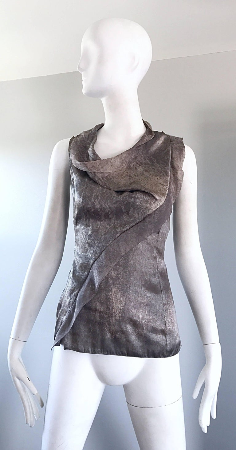Beautiful vintage GIORGIO ARMANI silver and gunmetal Avant Garde sleeveless shirt! Features luxurious silk, with a excellent draped neckline, and asymmetrical ruffle along the front bodice that drapes over the left shoulder. Hidden zipper up the