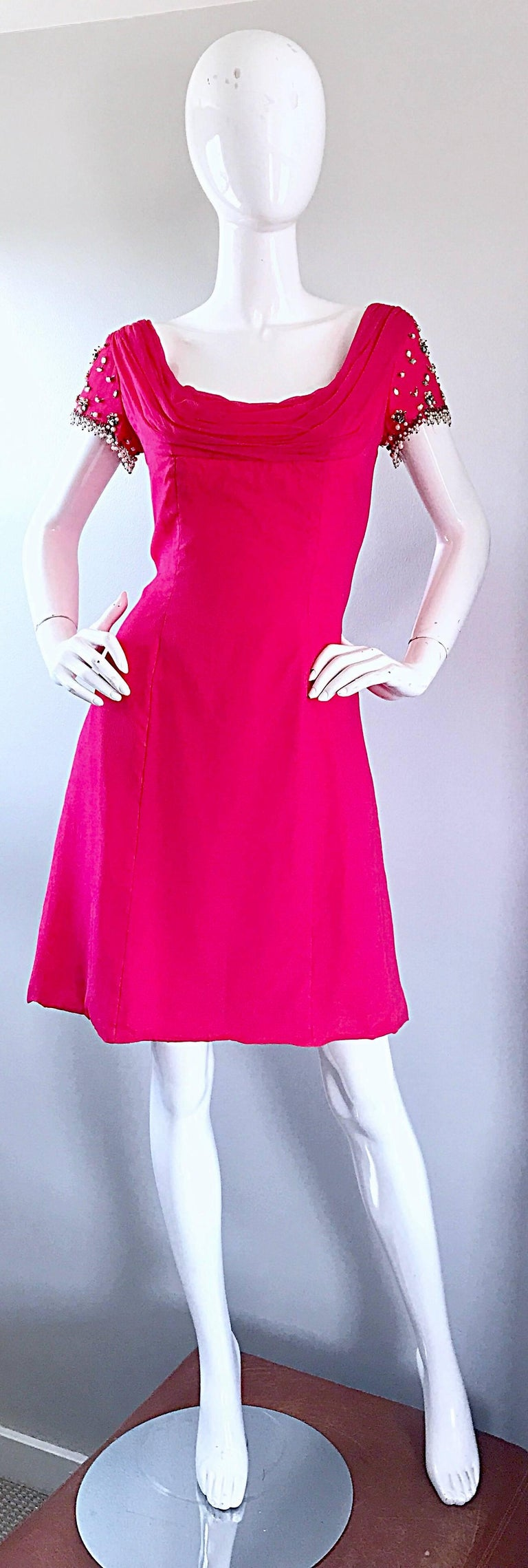 Beautiful early 1960s LILLI DIAMOND hot pink chiffon A-Line dress! Brand new with original store tags! Features hand-sewn beads, rhinestones and pearls on each sleeve. Full metal zipper up the back with hook-and-eye closure. Fitted bodice, with a