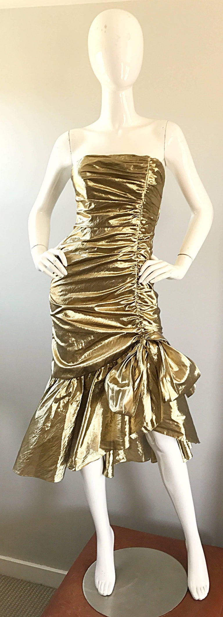 Amazing 1980s gold lame strapless Avant Garde cocktail dress! Features flattering ruched body, with an asymmetrical flared mermaid hem. Two panels tie to form a bow at the left hem. Hidden zipper up the back. Great belted or alone with heels or