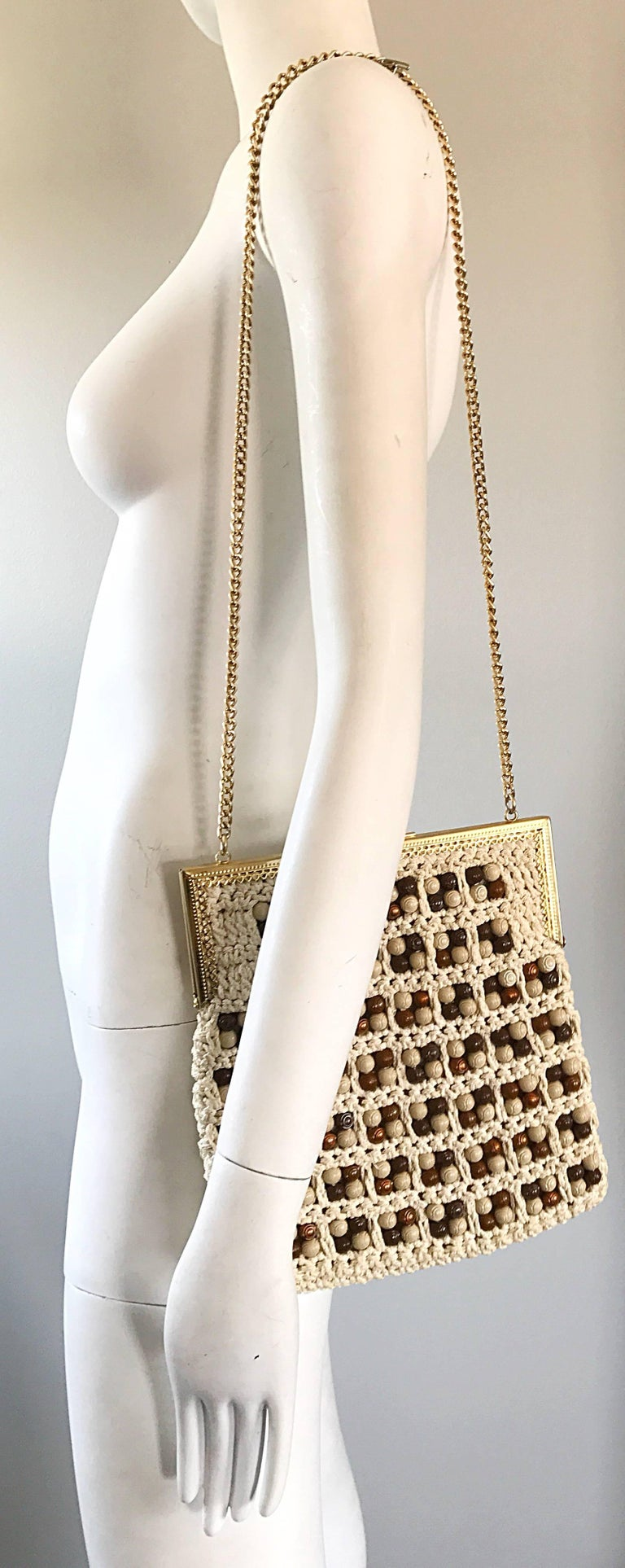 Chic 70s Italian ivory / white and brown hand crochet boho shoulder handbag! Features hundreds of brown wood looking beads on each side. The perfect size to fit all the essentials (smartphone, wallet, makeup, etc. Secure clasp closure. Gold chain