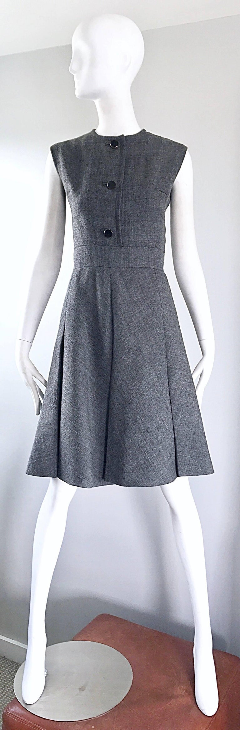 Stunning 1960s NINA RICCI HAUTE COUTURE gray wool A-Line dress and matching belted jacket suit! Jacket features the original black patent leather belt, and matching buttons. Two pockets at each side of the waist. Dress features a fitted bodice, and