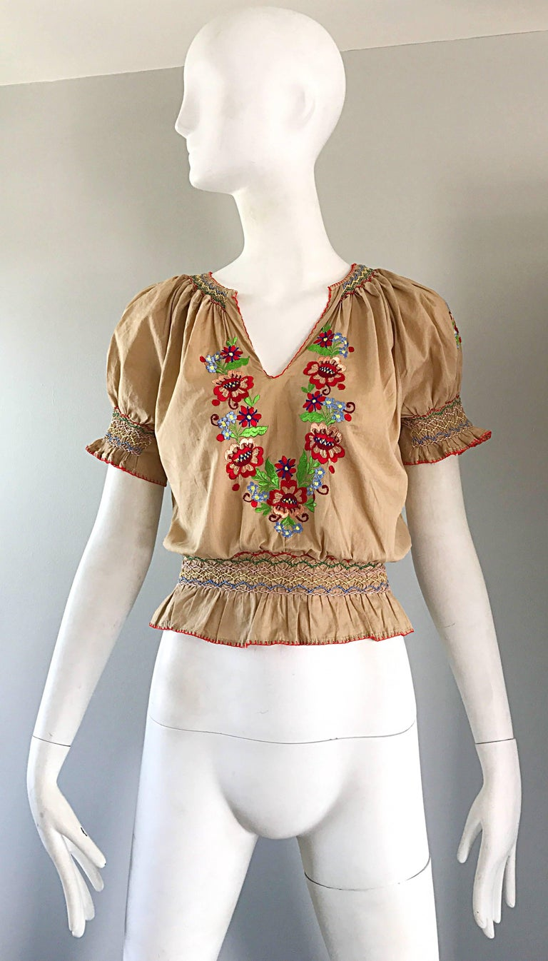 Rare and oh so chic 1940s Hungarian embroidered cotton cropped boho peasant shirt ! Classic light khaki tan color, with hand-sewn embroidered flowers in vibrant red, pink, yellow, green, blue, and white. Smocked detail at sleeve cuffs and at
