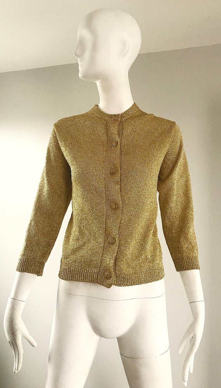 Chic 1950s gold metallic lurex 3/4 sleeves cardigan sweater! Features six gold metal buttons up the front, with hidden hook-and-eye closure at top neck. Fantastic tailored fit. Fantastic construction with lots of attention to detail. Can easily be