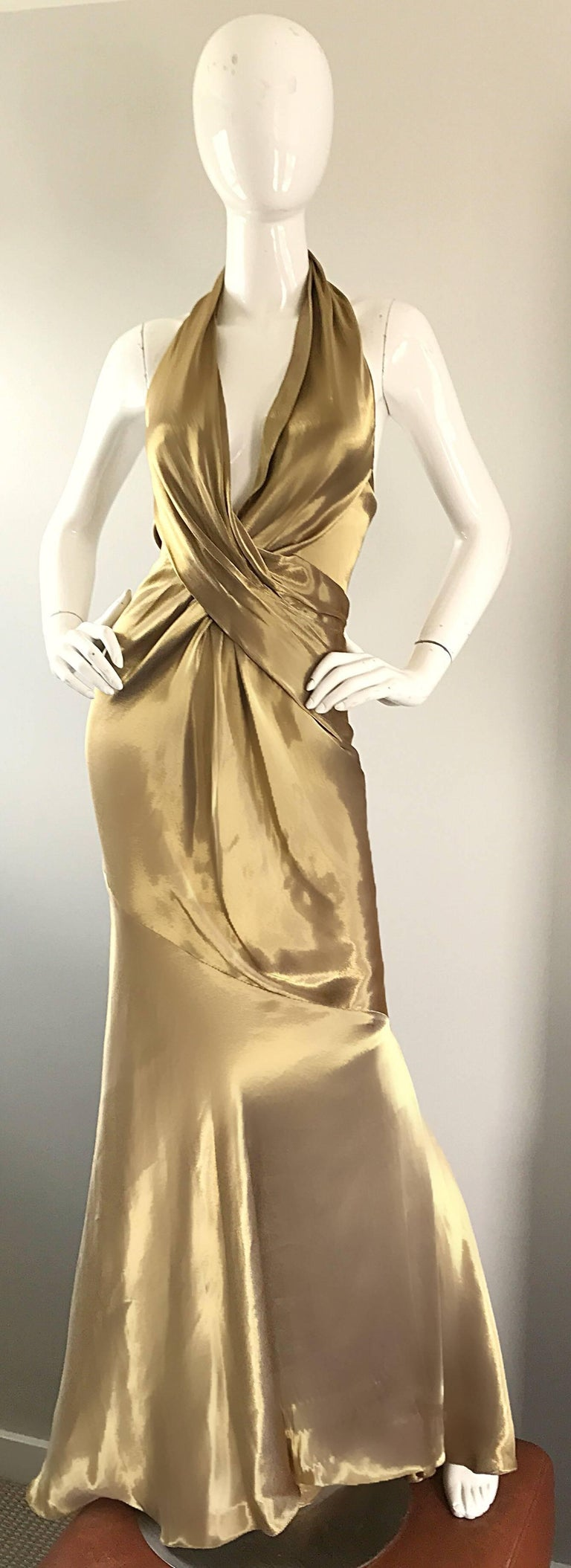 Stunning and sexy 1990s DONNA KARAN black label 'liquid gold' silk halter evening dress. Plunging neckline with an additional built in halter support. Hidden zipper up the side with multiple hook-and-eye closures. Flattering pleated bodice, with a
