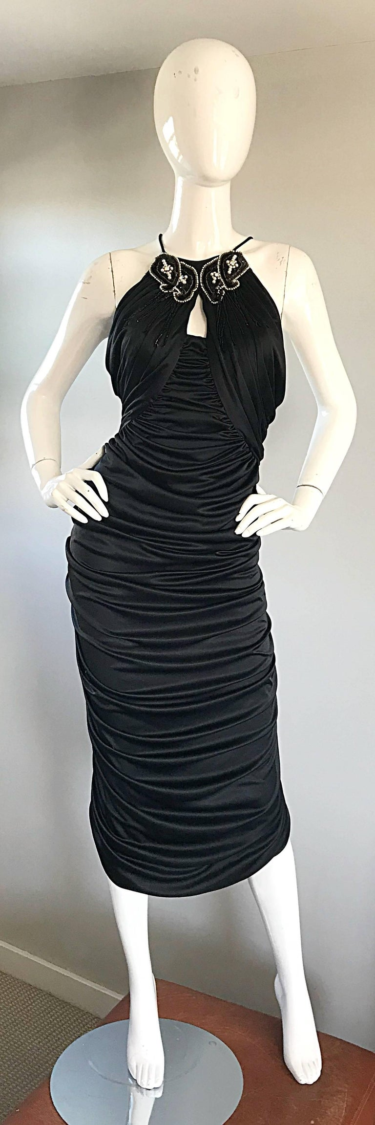 Sexy and super flattering SAMIR black ruched sleeveless cocktail dress! Features a peek-a-boo bust, encrusted with pearls, beads, seed beads and rhinestones. Flattering stretch jersey and ruching stretches to fit. Hidden zipper up the back.  In