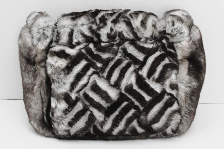 This authentic Limited Edition Chanel Chinchilla fur clutch looks and feels like no other handbag in the world. The luxuriously soft black & white fur covers the entire bag and blends perfectly with darkened silver Chanel