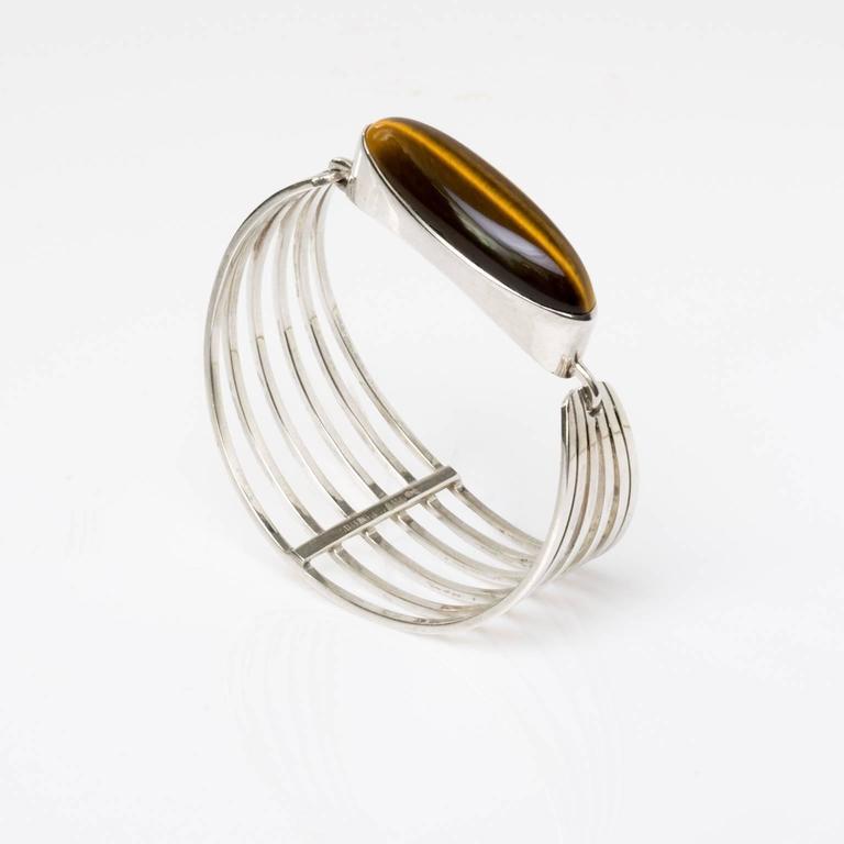 A stunning Scandinavian modern silver bracelet with an oblong tigers eye stone. Designed by Nobielle, 1970, Denmark.