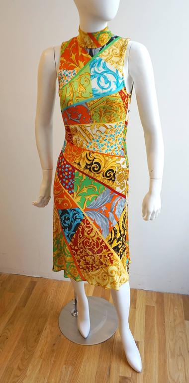 The print of this dressis quintessential VERSACE. The bold colors and prints are segmented and flare out from the right side of the waist. This highlights the body. There is a mock neck that is secured with double snaps on the back of the neck.
