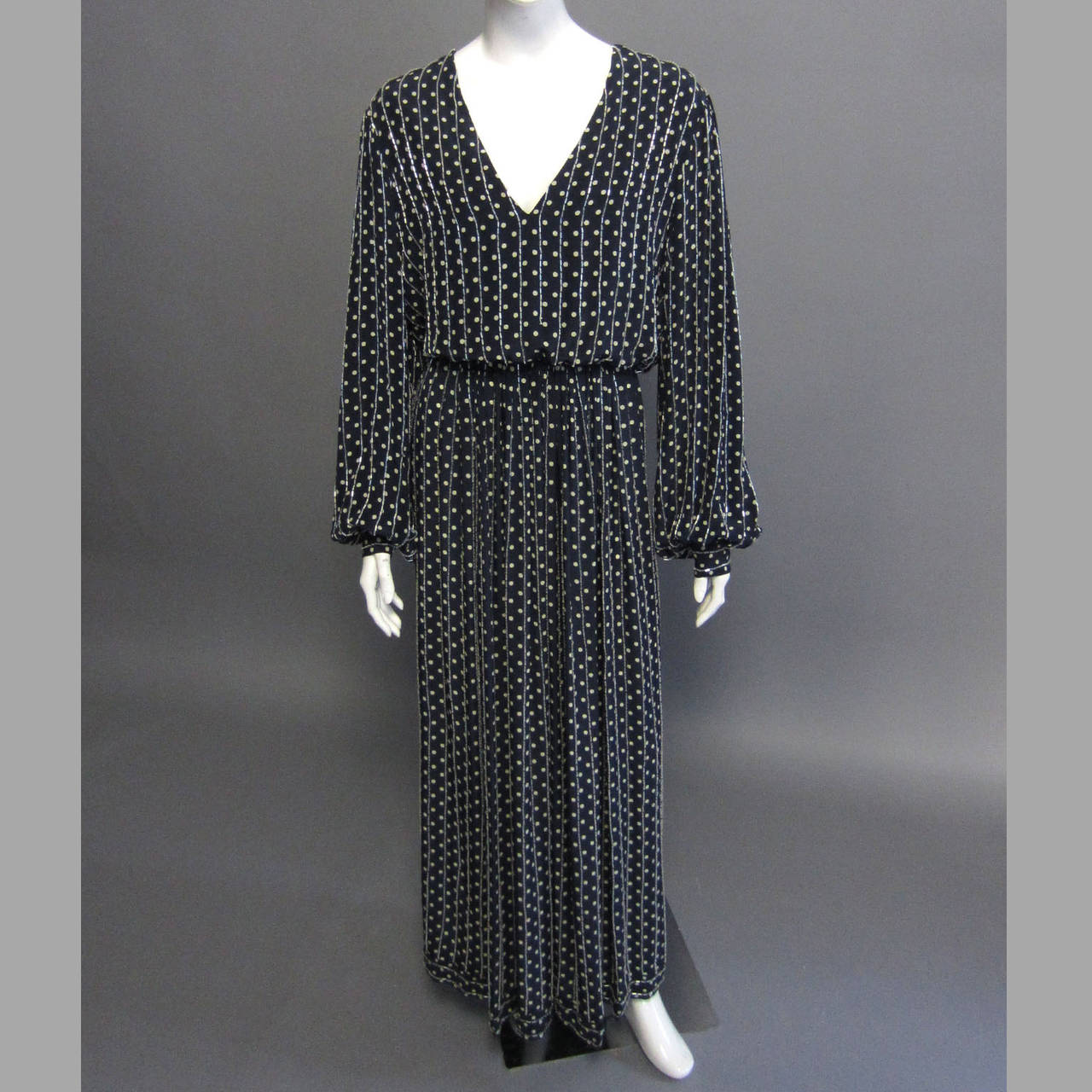 This Bill Blass gown features navy silk that is covered in a small, grey polka dot print. This print is accented by vertical, silver beading. The striped beadwork covers the entire gown. The long sleeves blouson over the 1.75