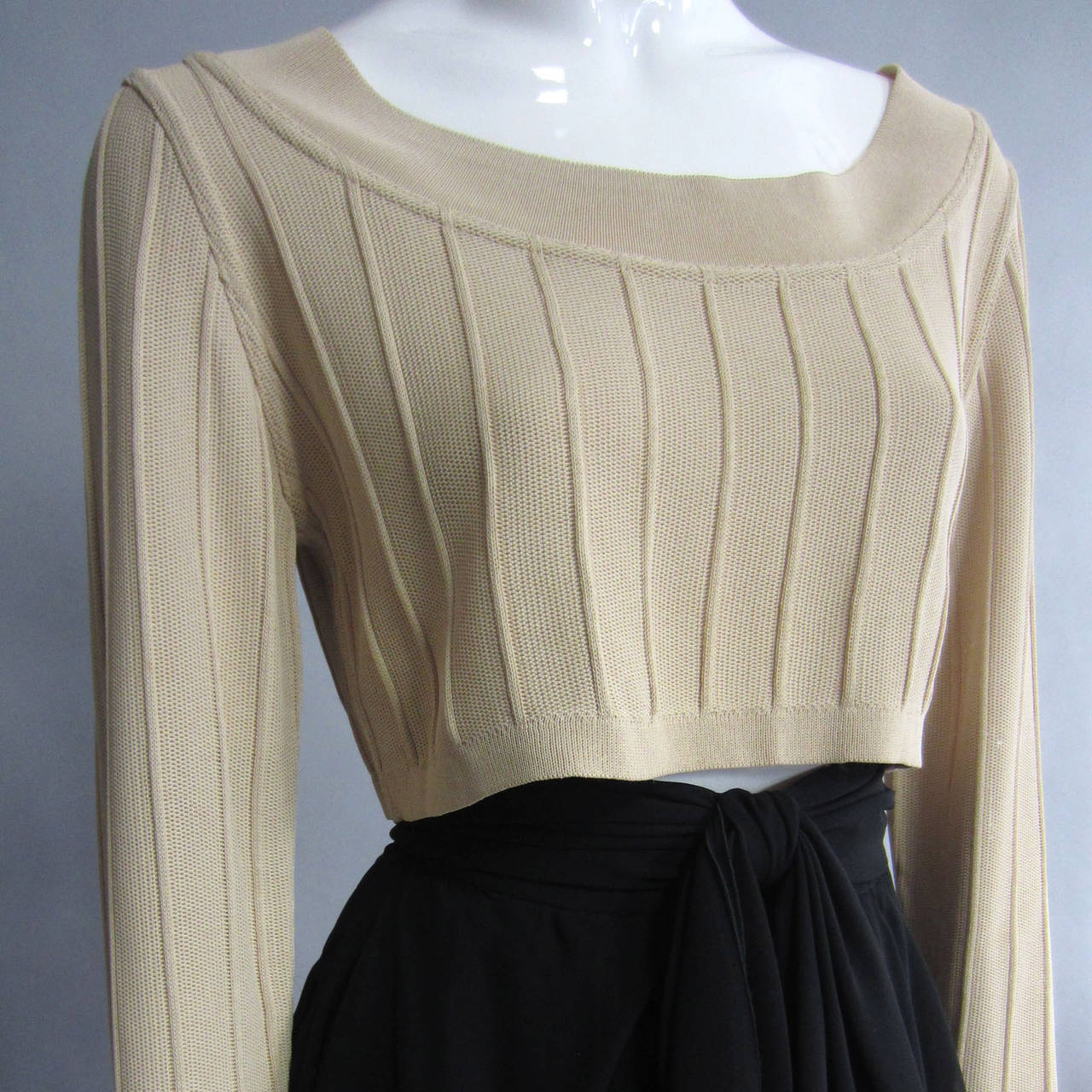 Essential ALAIA. This top has a wide, trimmed neckline. The body of the shirt features a wide set, thick, seam detailing. The vertical lines create length on this cropped shirt. Label Present. Measurements taken Unstretched.