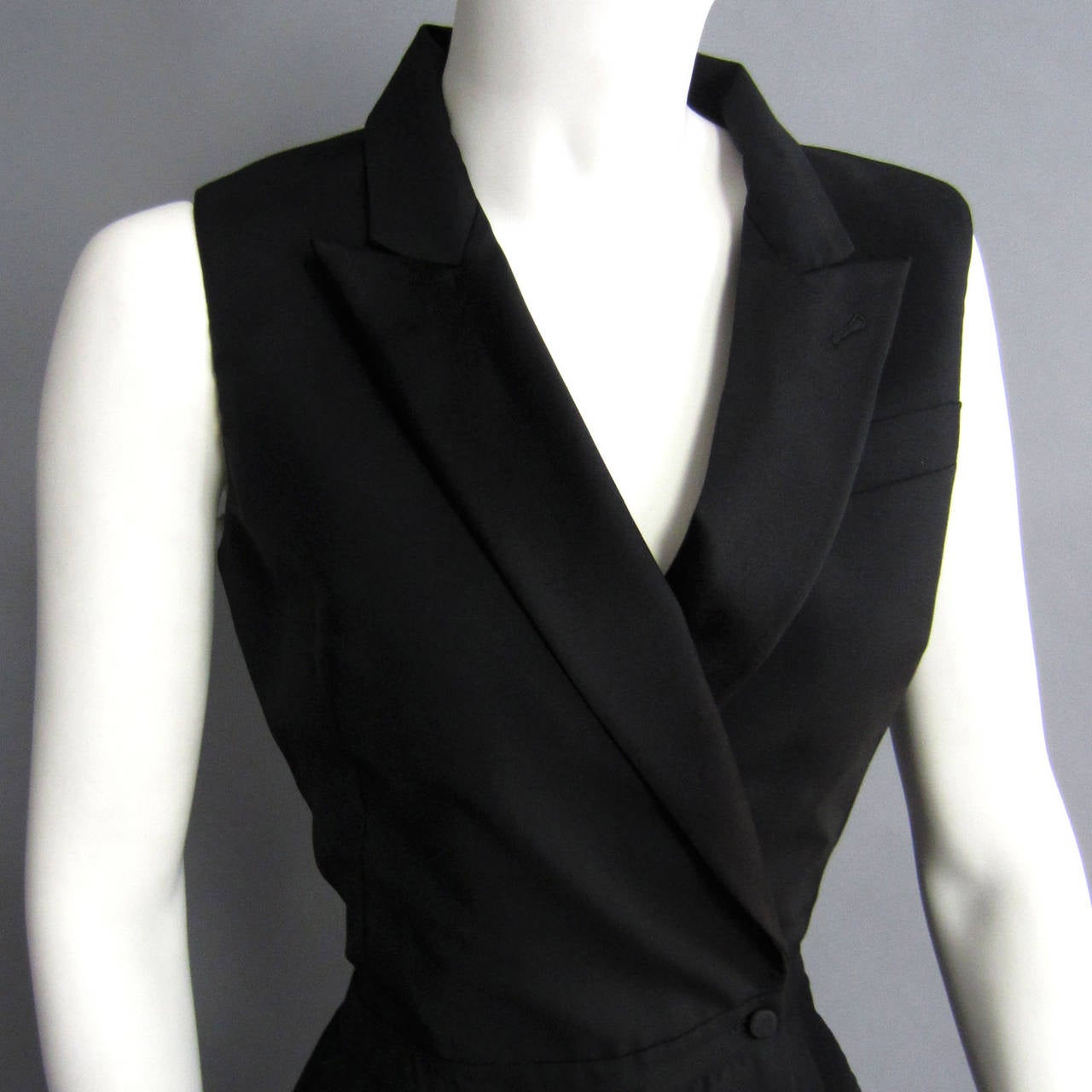 This ALEXANDER McQUEEN jumpsuit features a jacket style top. There is a satin lapel that frames the neckline. The top wraps over itself, with interior button closures on the waist. There is slight pleating to the pants, along with pockets on either