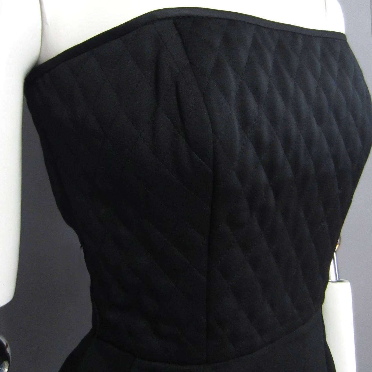 The perfect little black dress. This VICTOR COSTA features a quilted bodice. The top is trimmed in black silk. The simple skirt further accents the quilted detail. Simple and chic. Label Present. Excellent Condition.