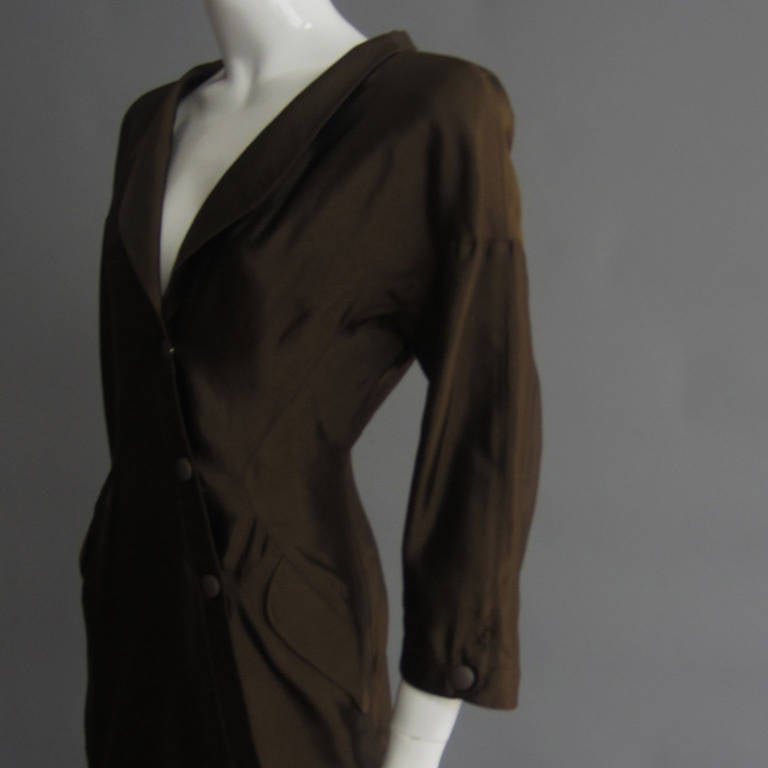 This Thierry Mugler creation is from the 1988 S/S Collection. The silk fabric produces a sheen that gives the brown color dimension. The deep, v neckline is accented with a thin, lapel detail and padded shoulders. The asymmetrical, snap closure