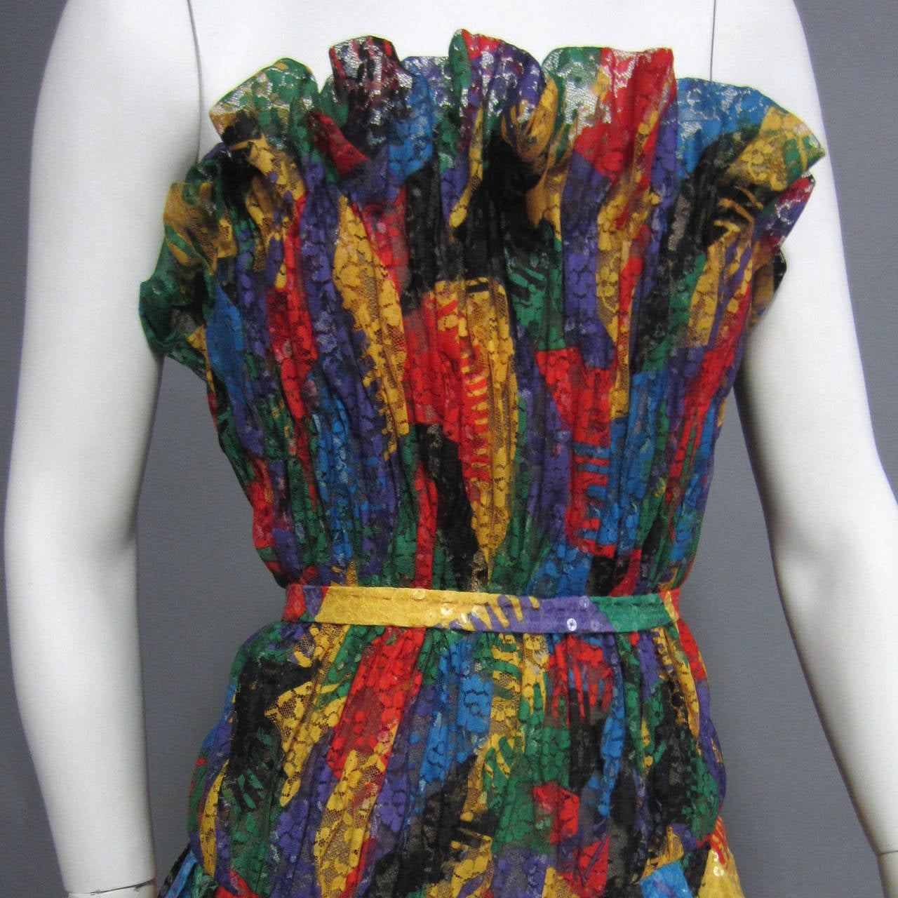 A kaleidoscope of colors and a mix of fabrics, this SCAASI dress has it all. The bodice is made of ruched, multi colored lace. Around the entire top of the bodice, the lace forms a ruffle detail. The lace is sheer, however the bodice is lined in a