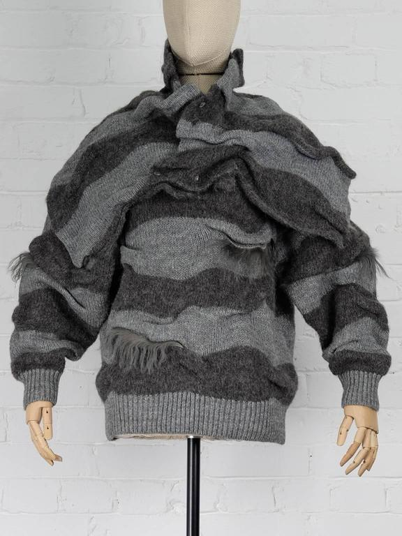 1980s Grey wool blend two piece striped jumper  featuring long sleeves, a ribbed hem and cuffs, a loose style, a detachable button fastening shawl and fur trims.   Total Lenght 58cm Bust 123cm Shoulders 55cm Sleeve 56cm