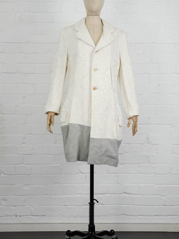 Cream wool contrast hem jacquard coat from Comme Des Garçons Vintage featuring notched lapels, a front button fastening, long sleeves, side flap pockets, a grey checked hem, a short length and a straight hem. Spring 1993