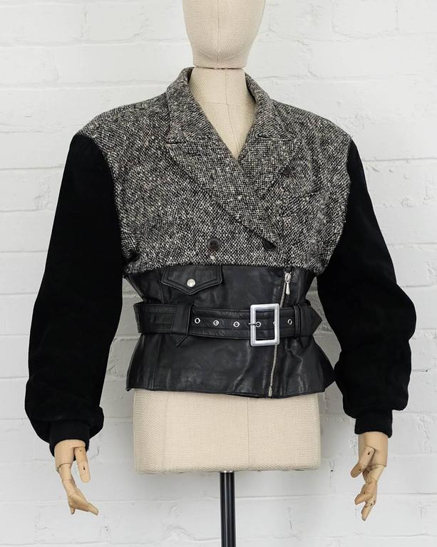 Black leather, suede and wool blend  biker jacket from Jean Paul Gaultier Vintage featuring notched lapels, a chest pocket, a double breasted front fastening, a belted waist, a front zip fastening, long sleeves, a grey tweed top and a press stud