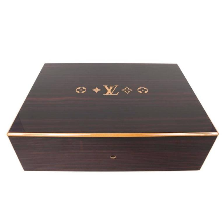 Elegant Louis Vuitton cigar case in mahogany finishing ebony wood. Capacity : 150 Ideal for a gift.  It is made of mahogany with ebony finish and a monogram: clover, LV, clover  in pear wood.  Material: mahogany with Macassar ebony veneer and pear