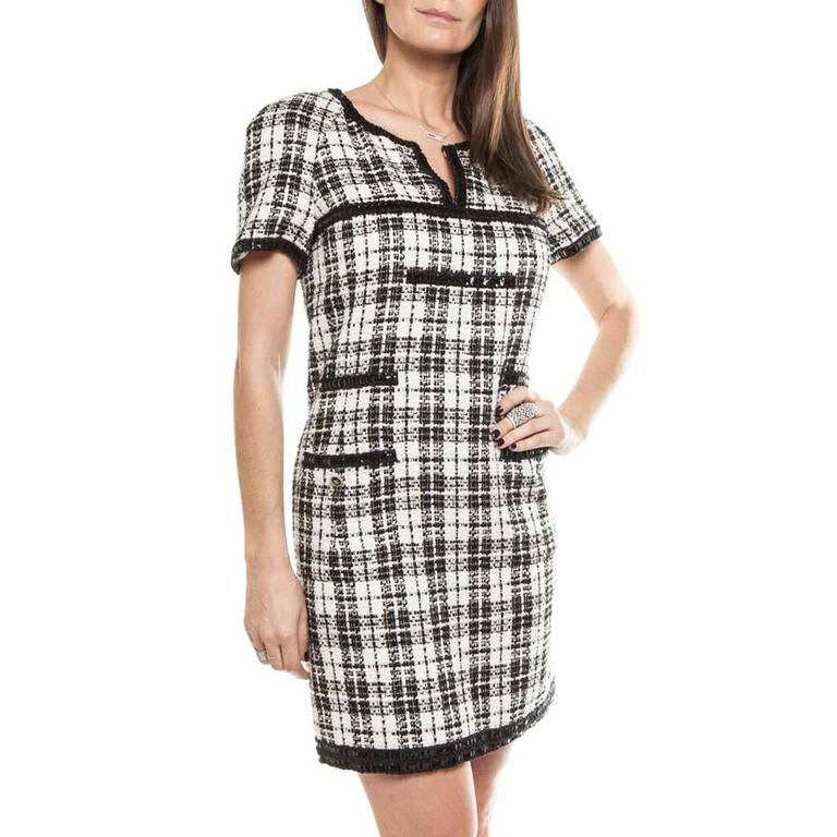 Chanel dress in black and white tweed.  The lining is made of natural silk. The collar is round and notched with a black polyester trim.  Spring 2007 Collection.  The raglan sleeves are short and the pockets are patched and edged with the same