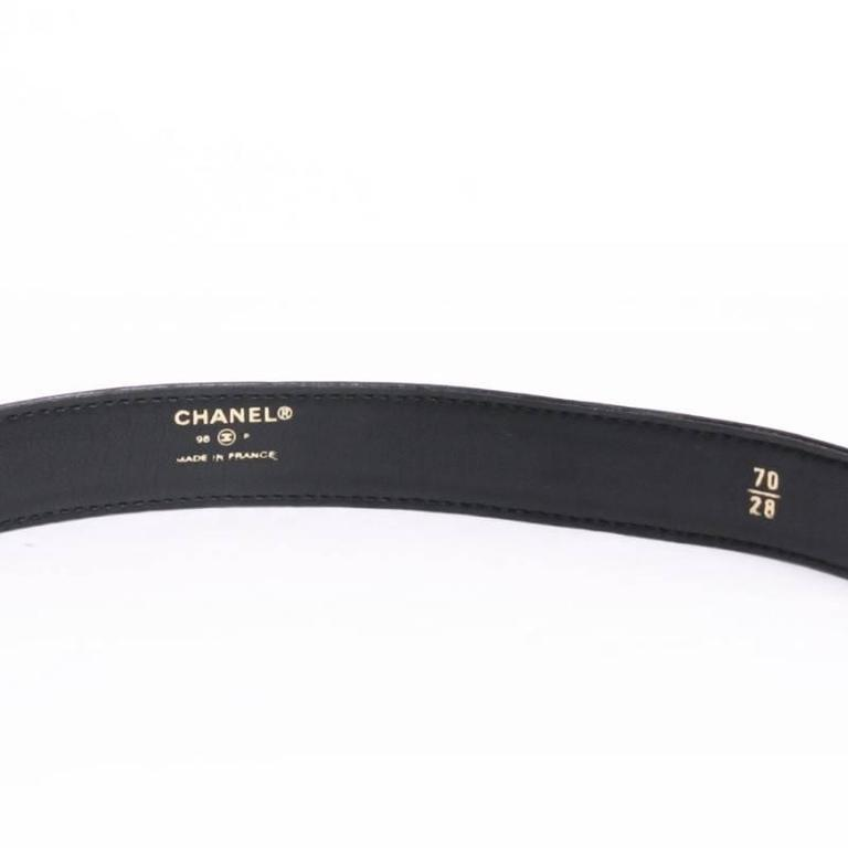 CHANEL belt in black leather.  The golden buckle bears the symbols of the Chanel house :  the 4-leaf clover, the camellia, 5, the 'CC' in gilt metal.  Delivered in a dustbag Valois Vintage Paris