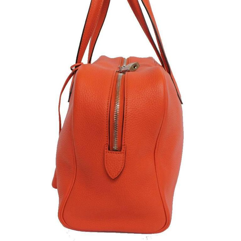 Hermes Victoria shoulder bag. It is in taurillon Clemence orange fire leather with a lining in chevron canvas. Letter R in a square (2014).  The fittings are in palladium silver finish with a zip closure.  It is worn by hand or on the shoulder.