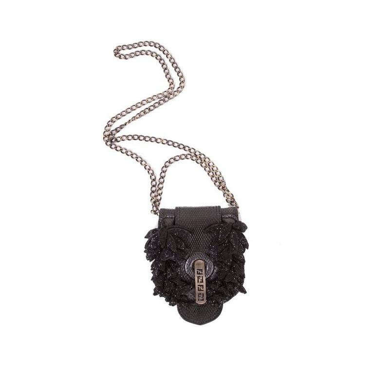 07ddf7cb7aee Mini FENDI flap bag in black snake leather. Metal hardware blackened and  coppered