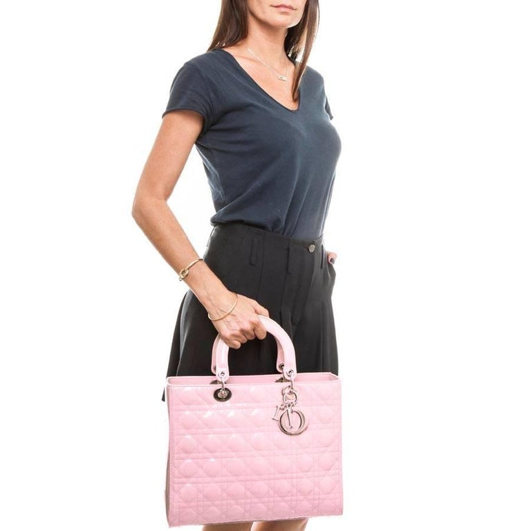 'Lady Dior' handbag in pastel pink patent leather. Palladium silver trim, zipper, 'CD' pendant, nails on the underside of the bag.   Worn hand with its 2 handles of 24 cm.  There is a removable shoulder strap for the shoulder or crossover of 82 cm.