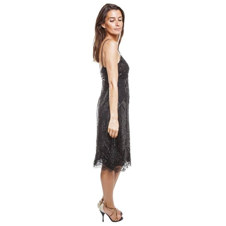 Cocktail dress black silk Valentino embroidered with lace of pearls and with sequins. Zipper on the left-hand side of the dress (38 cms in length).   It has a triple black fine silk lining.  Will be delivered in a cover
