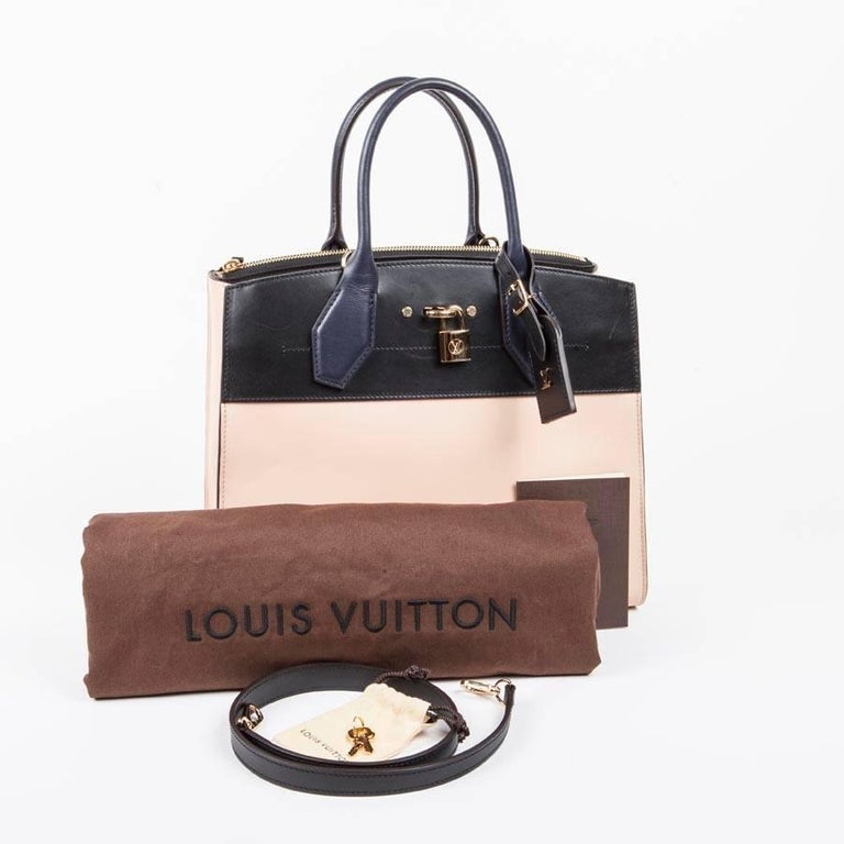 Louis Vuitton bag 'City steamer MM'  in tricolor beige and navy blue and black, smooth leather. Gilded metal parts. LV metal lettering address holder. Engraved padlock. Signature LV rim marked hot on the back.  Removable shoulder strap in 65 cm