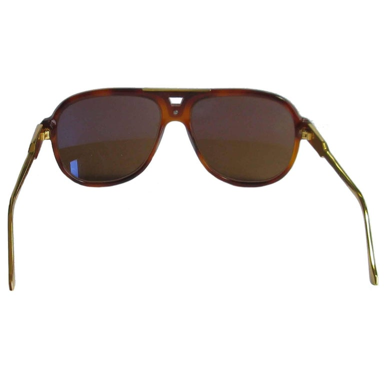 Sunglasses John Dalia 'Gary model' in tortoiseshell acetate. Glasses: dark brown. The branches are made of 24 karat gold.  Dimensions: frame width: 14,5 cm, height of the lenses: 4,8 cm, length of the branches: 13,5 cm  public price: 690 euros