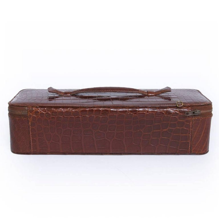 Vintage Hermes jewelry box in brown crocodile.   Zip closure.   The interior is in brown velvet with several compartments to store your precious jewels.