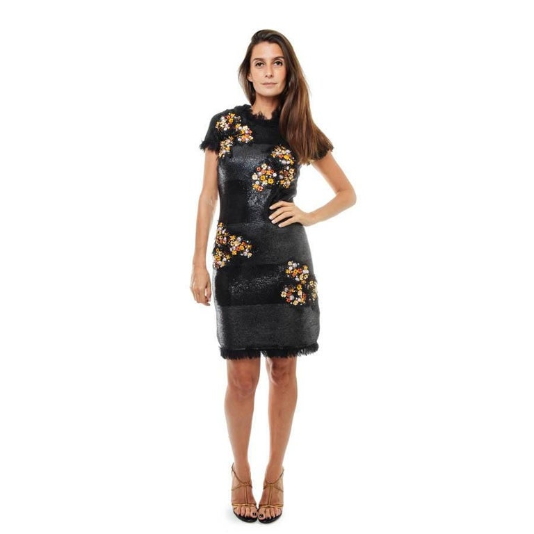 Chanel 'Paris Monaco' collection black embroidered dress in wool and silk.  The dress is black laced and embroidered with orange and gold flowers on the front. Sleeves are short and there are small tulle fringes around the collar, the sleeves as
