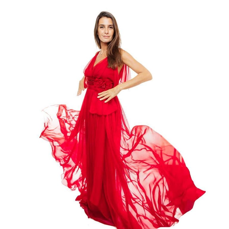Elie Saab evening gown in red chiffon. It is embroidered under the chest with iridescent red sequins, embellished with a muslin and sequins flowers. Zip closure in the back.  It is lined with red dry silk.  Dimensions flat: under the armpits 36 cm,