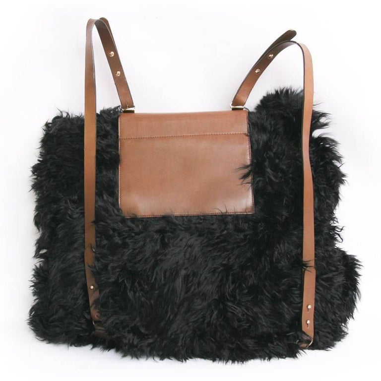 Original! Marni backpack, big model in black fur. The trim is made of natural leather. The hardware is in gilded metal. The interior is in beige canvas with a large zipped pocket.  It can be tightened with two leather straps. It has a rigid flap