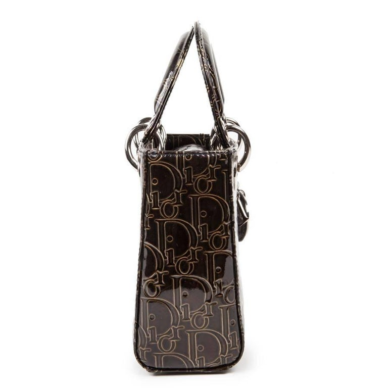 Collector. Lady Dior mini handbag in copper brown patent leather with oblique printed golden DIOR all over the bag.  The interior is black satin canvas and a zipped pocket. Silver hardware.  Will be delivered in its original box.