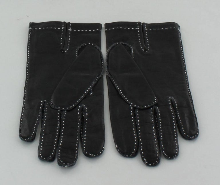 HERMES gloves in black smooth leather with white saddle stitching. Slight clefts in the palm of the hand.  Dimensions: Width: 8cm, Length: 23cm