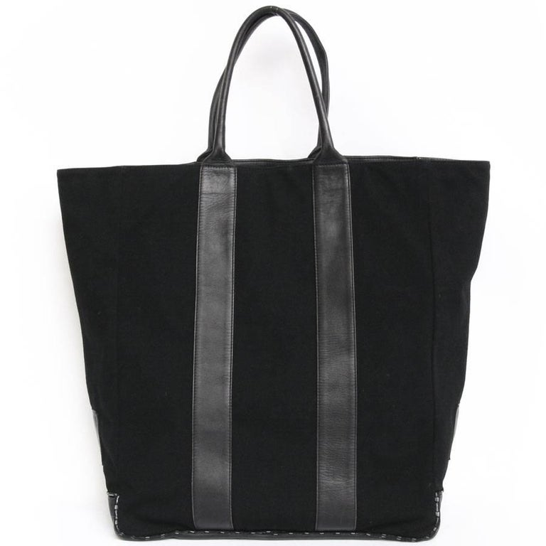 Beautiful Chanel tote bag in black leather and jersey. It has 2 inside pockets.  dimensions : Leather handles: 42cm  Included : Hologram: 844 **** (year 2004)  Delivered in a CHANEL dustbag