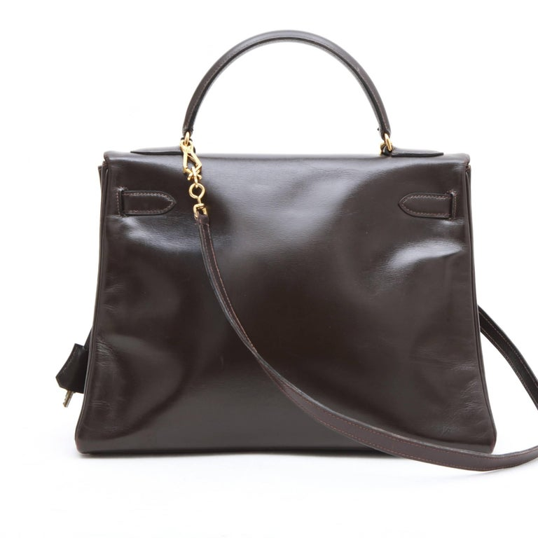 Hermes Kelly 32 bag in brown box leather. Gilded hardware.  Worn by hand or on the shoulder with a removable shoulder strap of 83 cm.  No stamp behind the tongue, vintage bag. The interior is lined with the same leather with 1 zipped poach and two