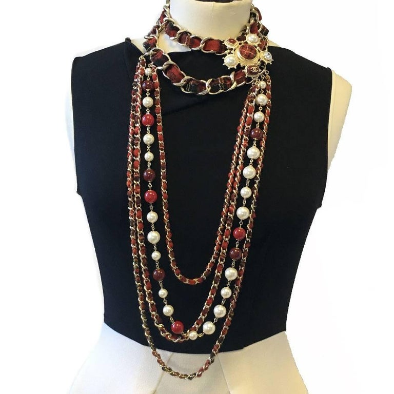 Beautiful Chanel necklace from 'Paris-Edinburgh' Métiers d'Arts 2013 collection.  Red tweed long necklace, row of pearly pearls and red molten glass, 4 gold metal chains interlaced with red tweed.  A beautiful jewel is on the left side. It is made