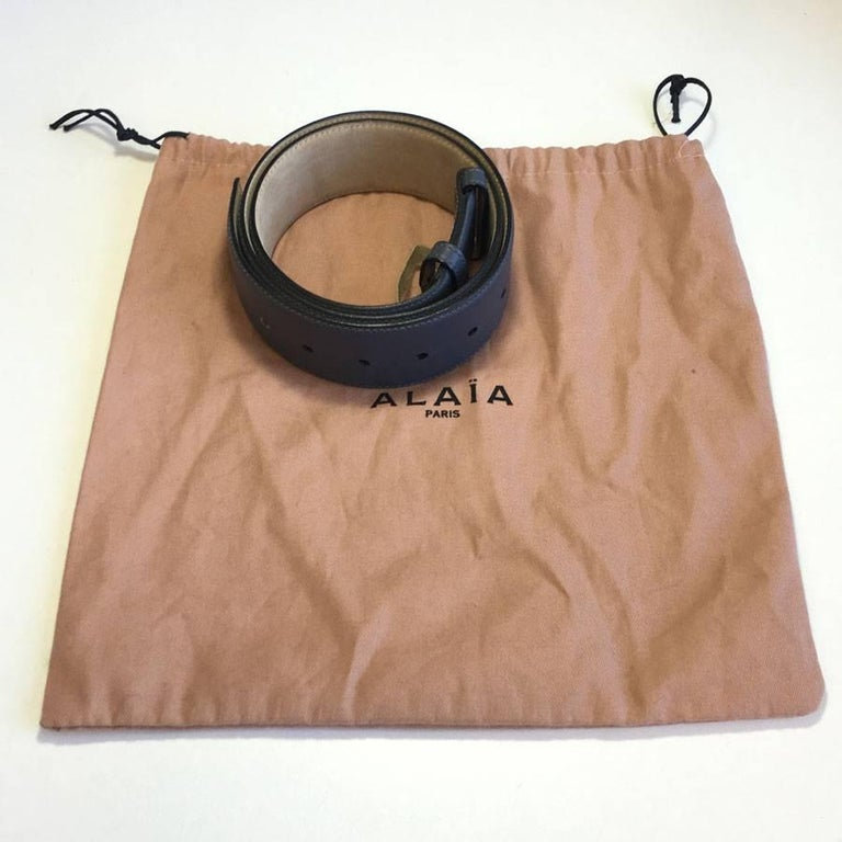 ALAÏA belt in dark gray leather, beige suede interior. Size 75FR. In very good condition. A tiny scratch on the gray leather (see photo).  Dimensions: shortest: 70 cm - longest: 82.5 cm - width: 5 cm  Will be delivered in its ALAÏA pouch.
