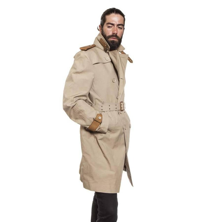 Very rare. Burberry trench coat for riding in beige cotton and natural leather and logo buttons. Numerous details on the belt, on the wrists and on the shoulders. At the back there is a leather overbelt. Inside there is a leather to tighten the