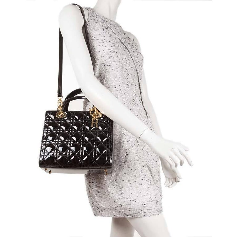 Christian Dior 'Lady Dior' bag in black quilted patent leather. Gilded metal hardware. Zip closure.  Worn by hand carried with two handles or on the shoulder with a removable shoulder strap The interior is made of fabric red with a zipped
