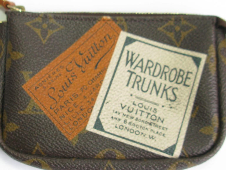 Mini pouch - keychain Louis Vuitton 'Wardrobe Trunk' in brown monogram canvas. There are prints of classic trunks and advertising stickers.  Zipped pocket, gilt metal clip for keys.  In very good condition. Made in Spain. Authentication number: